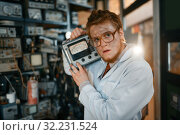 Купить «Scientist in glasses holds electrical device», фото № 32231524, снято 17 июня 2019 г. (c) Tryapitsyn Sergiy / Фотобанк Лори