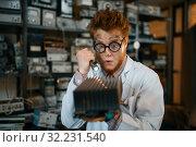 Купить «Strange engineer examines the cooling radiator», фото № 32231540, снято 17 июня 2019 г. (c) Tryapitsyn Sergiy / Фотобанк Лори