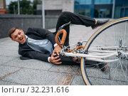 Businessman fell off his bike at office building. Стоковое фото, фотограф Tryapitsyn Sergiy / Фотобанк Лори