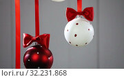 Купить «Christmas balls hanging with ribbons», видеоролик № 32231868, снято 28 сентября 2019 г. (c) Иван Михайлов / Фотобанк Лори