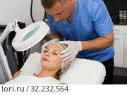 Купить «Man doctor is analysing skin on face of female patient before the procedure», фото № 32232564, снято 7 августа 2017 г. (c) Яков Филимонов / Фотобанк Лори