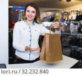 Купить «Happy woman seller showing numerous purchases», фото № 32232840, снято 20 марта 2017 г. (c) Яков Филимонов / Фотобанк Лори