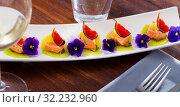 Купить «Ceviche from pickled red fish and cumquat a circle of kiwi, with figs at plate», фото № 32232960, снято 21 октября 2019 г. (c) Яков Филимонов / Фотобанк Лори
