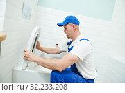 Plumber service. handyman installing toilet sink. Стоковое фото, фотограф Дмитрий Калиновский / Фотобанк Лори