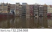 Купить «Старинные узкие дома на городском канале облачным сентябрьским днем. Амстердам, Нидерланды», видеоролик № 32234068, снято 30 сентября 2017 г. (c) Виктор Карасев / Фотобанк Лори