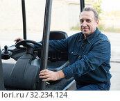 Купить «Worker goes driving loader», фото № 32234124, снято 12 октября 2016 г. (c) Яков Филимонов / Фотобанк Лори