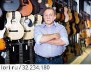Купить «Mature man choosing acoustic guitar», фото № 32234180, снято 18 сентября 2017 г. (c) Яков Филимонов / Фотобанк Лори