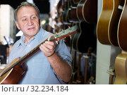 Купить «Man looking new wooden acoustic guitar in studio», фото № 32234184, снято 18 сентября 2017 г. (c) Яков Филимонов / Фотобанк Лори