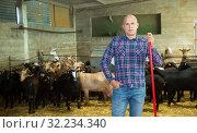 Купить «Farmer does the cleaning in the goat shed», фото № 32234340, снято 15 декабря 2018 г. (c) Яков Филимонов / Фотобанк Лори