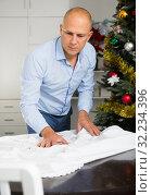 Купить «Man spreading tablecloth on table», фото № 32234396, снято 10 января 2019 г. (c) Яков Филимонов / Фотобанк Лори