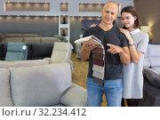 Купить «Couple holding samples of upholstery fabric», фото № 32234412, снято 29 октября 2018 г. (c) Яков Филимонов / Фотобанк Лори