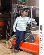 Купить «African American man standing near forklift at fruit warehouse», фото № 32234488, снято 15 декабря 2018 г. (c) Яков Филимонов / Фотобанк Лори