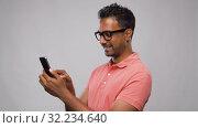 Купить «happy indian man in glasses using smartphone», видеоролик № 32234640, снято 17 сентября 2019 г. (c) Syda Productions / Фотобанк Лори