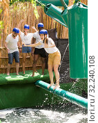 Купить «Young people try to walk the wet log in the theme park», фото № 32240108, снято 5 июля 2020 г. (c) Яков Филимонов / Фотобанк Лори
