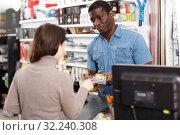 Attentive salesman offering tools to young woman. Стоковое фото, фотограф Яков Филимонов / Фотобанк Лори