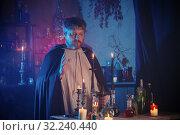 Купить «portrait of wizard with burning candles and magic potions», фото № 32240440, снято 14 августа 2019 г. (c) Майя Крученкова / Фотобанк Лори