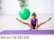 Купить «Little girl gymnast doing exercises indoors», фото № 32241232, снято 16 июля 2019 г. (c) Elnur / Фотобанк Лори
