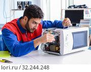 Купить «The young repairman fixing and repairing microwave oven», фото № 32244248, снято 11 июля 2017 г. (c) Elnur / Фотобанк Лори