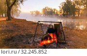 A bonfire on the bank of the river against a background of a foggy morning. Стоковое фото, фотограф Акиньшин Владимир / Фотобанк Лори