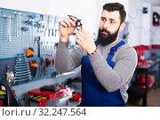 Купить «Worker motorcycle repair inspects the item», фото № 32247564, снято 5 декабря 2019 г. (c) Яков Филимонов / Фотобанк Лори
