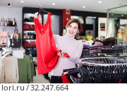 Купить «Glad customer deciding on pretty blouse», фото № 32247664, снято 7 февраля 2017 г. (c) Яков Филимонов / Фотобанк Лори