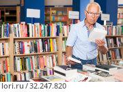 Купить «Older man choosing books in bookstore», фото № 32247820, снято 11 июня 2018 г. (c) Яков Филимонов / Фотобанк Лори