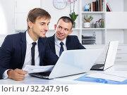 Купить «two smiling men coworkers working in firm office», фото № 32247916, снято 31 мая 2020 г. (c) Яков Филимонов / Фотобанк Лори