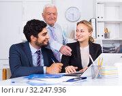 Купить «Office workers are demonstrating reports on laptop to mature boss», фото № 32247936, снято 27 июня 2017 г. (c) Яков Филимонов / Фотобанк Лори