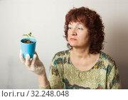 Купить «A female gardener shows a pot with sprouts after a pick.», фото № 32248048, снято 3 апреля 2016 г. (c) Акиньшин Владимир / Фотобанк Лори