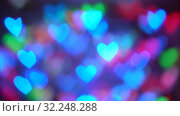 Garland burn and flicker in soft defocused bokeh. Blurred bokeh in form of hearts of New Year's flickering garlands. Festive mood. Christmas or New Year background. Стоковое видео, видеограф Dmitry Domashenko / Фотобанк Лори