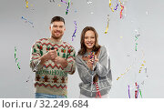 couple in christmas sweaters popping party poppers. Стоковое фото, фотограф Syda Productions / Фотобанк Лори