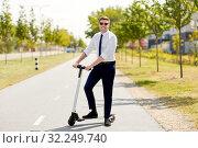 Купить «young businessman riding electric scooter in city», фото № 32249740, снято 1 августа 2019 г. (c) Syda Productions / Фотобанк Лори