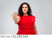 Купить «woman in red dress showing stop gesture», фото № 32249924, снято 15 сентября 2019 г. (c) Syda Productions / Фотобанк Лори