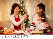Купить «happy family taking picture at christmas dinner», фото № 32249976, снято 11 января 2018 г. (c) Syda Productions / Фотобанк Лори