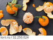 Купить «close up of peeled mandarins on slate table top», фото № 32250024, снято 5 апреля 2018 г. (c) Syda Productions / Фотобанк Лори