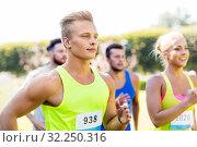 Купить «happy young sportsmen racing wit badge numbers», фото № 32250316, снято 16 августа 2015 г. (c) Syda Productions / Фотобанк Лори