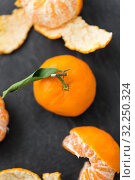 Купить «close up of peeled mandarins on slate table top», фото № 32250324, снято 5 апреля 2018 г. (c) Syda Productions / Фотобанк Лори