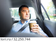 businessman with takeaway coffee on car back seat. Стоковое фото, фотограф Syda Productions / Фотобанк Лори