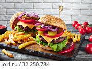 Купить «Hamburgers with cheddar cheese on a board», фото № 32250784, снято 14 июня 2019 г. (c) Oksana Zh / Фотобанк Лори