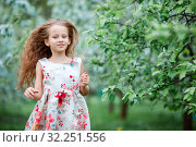 Купить «Adorable little girl in blooming apple tree garden on spring day», фото № 32251556, снято 10 мая 2016 г. (c) Дмитрий Травников / Фотобанк Лори