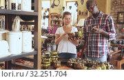 Купить «Loving happy couple choosing stoneware in pottery store», видеоролик № 32251704, снято 15 ноября 2019 г. (c) Яков Филимонов / Фотобанк Лори