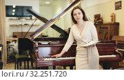 Купить «Pretty woman seller in piano music store», видеоролик № 32251720, снято 12 мая 2019 г. (c) Яков Филимонов / Фотобанк Лори