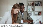 Купить «Young woman and man colleagues working at laptop and discussing in office», видеоролик № 32251728, снято 26 апреля 2019 г. (c) Яков Филимонов / Фотобанк Лори