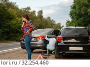 Male and female drivers on road, car accident. Стоковое фото, фотограф Tryapitsyn Sergiy / Фотобанк Лори