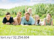 Portrait of large family lying on green lawn outdoors. Стоковое фото, фотограф Яков Филимонов / Фотобанк Лори