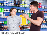 Купить «Smiling sporty guy and girl talking about food supplements in sport nutrition store», фото № 32254924, снято 12 апреля 2018 г. (c) Яков Филимонов / Фотобанк Лори