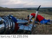 Купить «Sword stuck in the ground and metal knight helmet», фото № 32255016, снято 5 июля 2019 г. (c) Tryapitsyn Sergiy / Фотобанк Лори