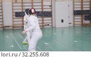 Купить «Two young women having an active fencing training in the school gym», видеоролик № 32255608, снято 1 апреля 2020 г. (c) Константин Шишкин / Фотобанк Лори
