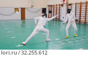 Two young women in protective helmets having an active fencing training in the school gym - making lunges on each other. Стоковое видео, видеограф Константин Шишкин / Фотобанк Лори