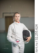 Купить «A young smiling woman fencer standing in the gym holding sword and helmet», фото № 32255624, снято 5 октября 2019 г. (c) Константин Шишкин / Фотобанк Лори